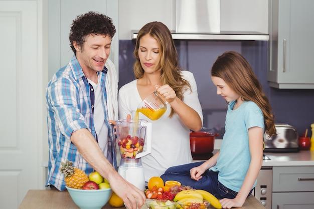 Семья готовит фруктовый сок
