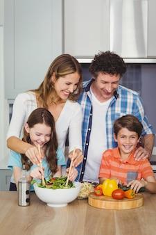 野菜サラダを準備する幸せな家族
