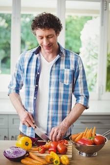 若い男が自宅で野菜を切る