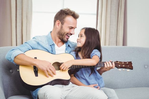 Мужчина играет на гитаре с дочерью дома