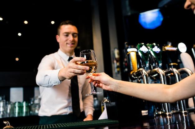 バーでクライアントに白ワインのグラスを与えるバーテンダーの笑みを浮かべてください。