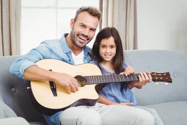 自宅で娘とギターを弾く男
