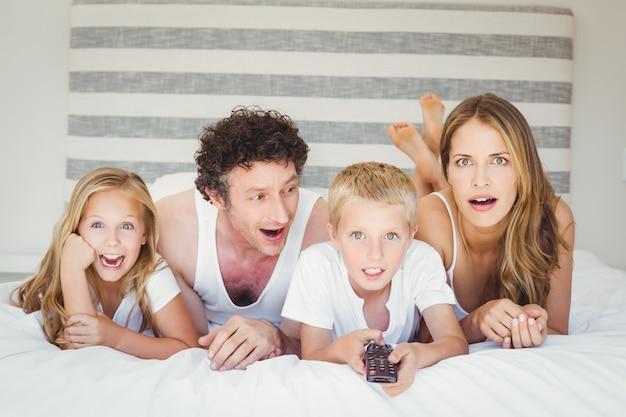 Семья отдыхает на кровати у себя дома