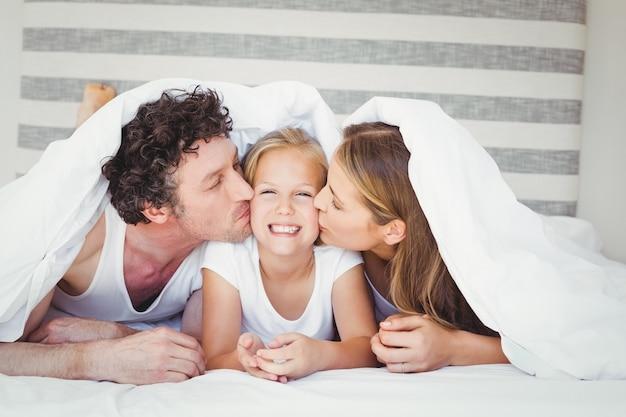 布団で覆われた娘にキスする両親