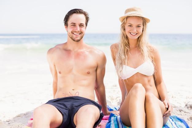 ビーチに座っている若いカップルの肖像画