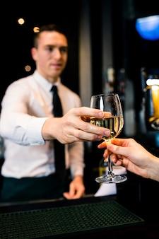 バーテンダーがバーでお客様に飲み物を与える