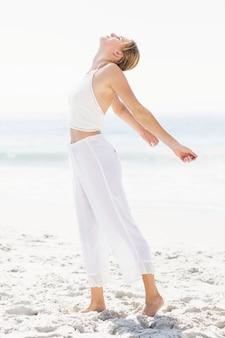 ビーチで彼女の腕を伸ばして美しい女性