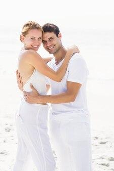 ビーチでお互いを受け入れて幸せなカップルの肖像画