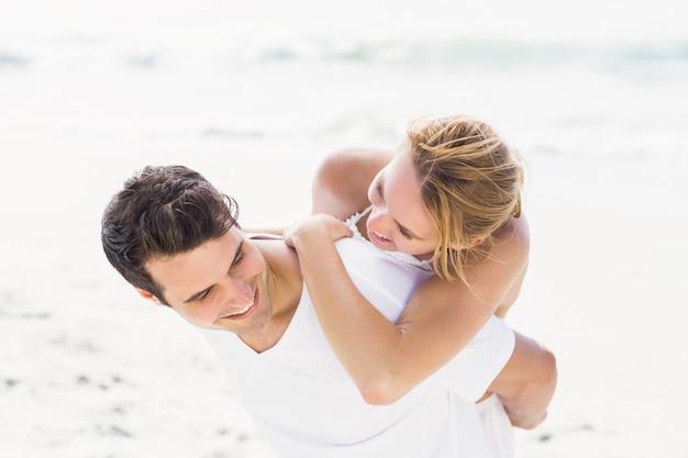 ビーチで女性にピギーバックを与える男