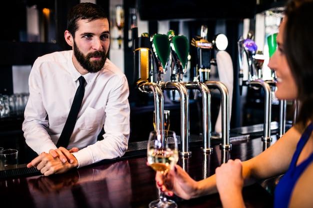 バーテンダーがバーでかなりの顧客と話しています。