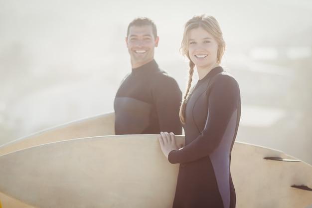 ビーチに立っているサーフボードとカップルの肖像画