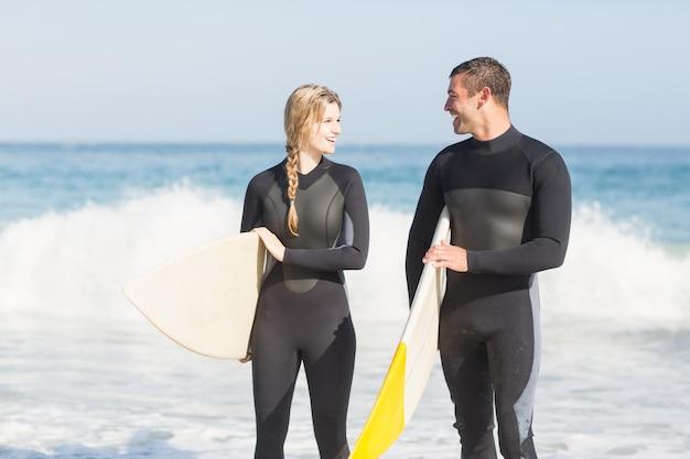 カップルはビーチの上を歩いてサーフボード