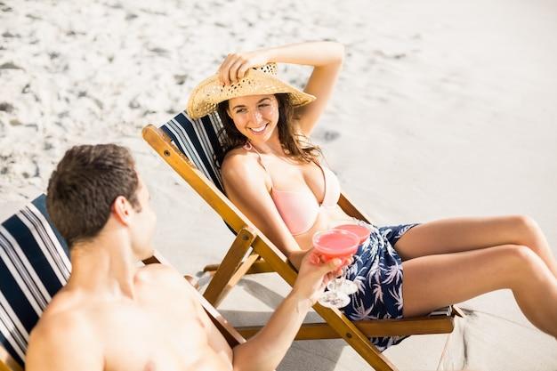 カクテルを飲むと肘掛け椅子に座っている若いカップル