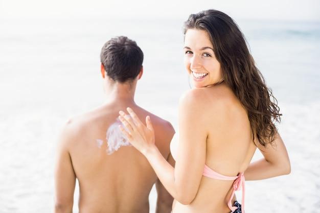 Женщина наносит солнцезащитный лосьон на спину мужчины