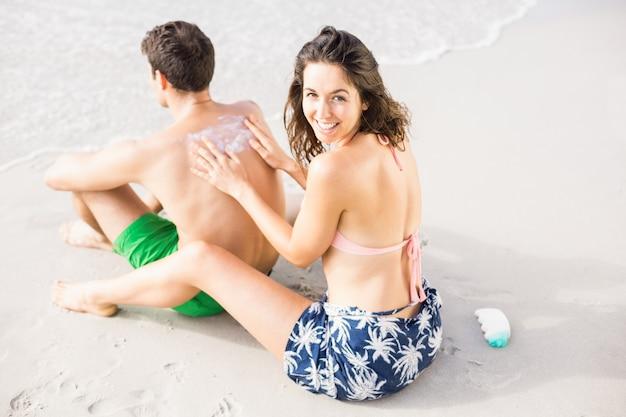 女性の背中に日焼け止めローションを適用する