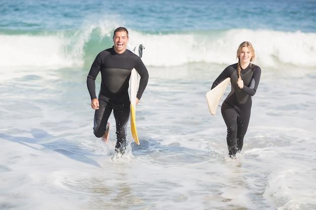 カップルはビーチで実行されているサーフボード