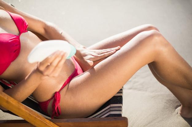 肘掛け椅子に座って日焼け止めローションを適用する女性の中央部