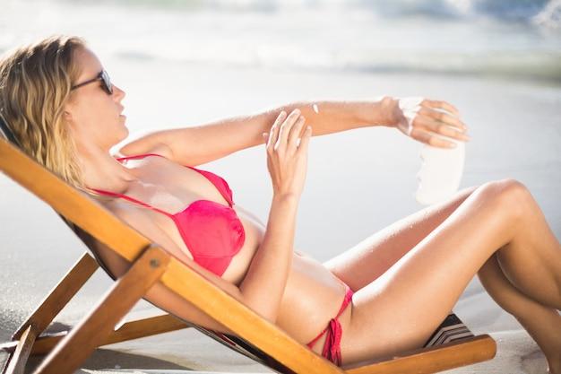 女性は肘掛け椅子に座って、日焼け止めローションを適用します