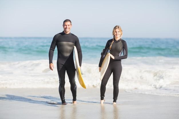 ビーチの上を歩くサーフボードとカップルの肖像画