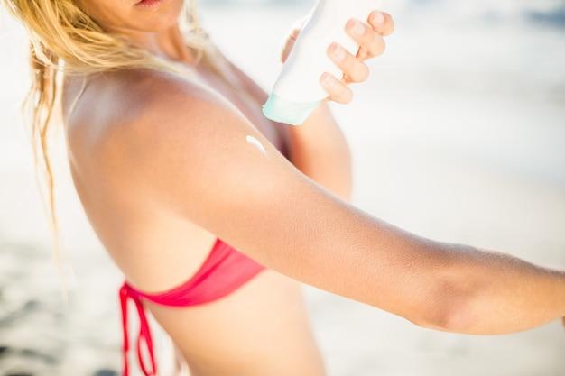 ビーチで日焼け止めローションを適用する女性の中央部