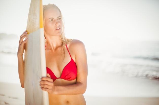 Женщина в бикини стоит с доской для серфинга на пляже