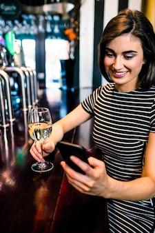 女性が酒を飲むとバーでスマートフォンを使用して