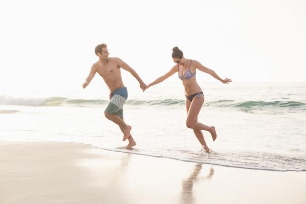 ビーチを走る幸せなカップル