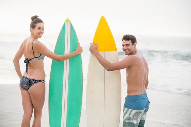 カップルはビーチでサーフボードに立って