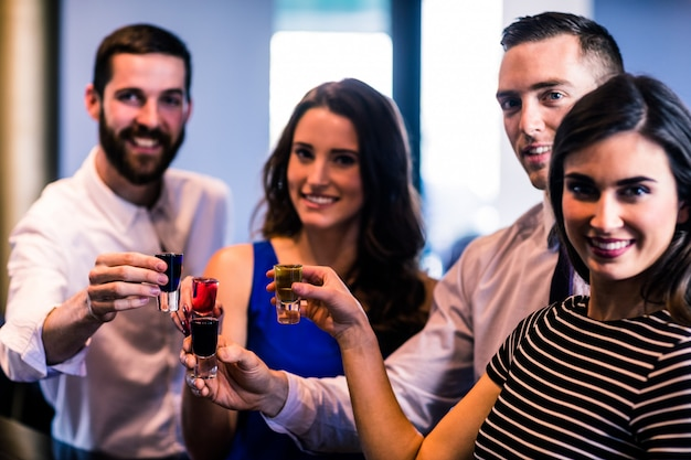 Друзья тостов с алкогольными выстрелами в баре