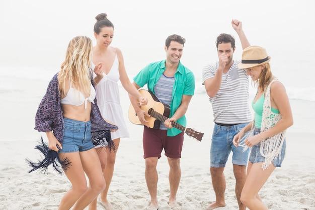 Группа друзей играет на гитаре и танцы