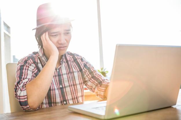 オフィスでラップトップを使用して心配している流行に敏感なビジネスマン