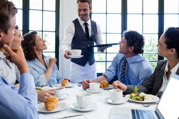 ビジネスの人々にコーヒーを提供するウェイター