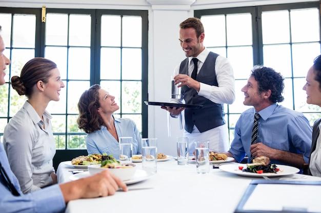 Официант подает воду для деловых людей