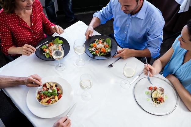 昼食を食べながら話している友人のグループ