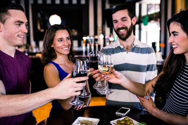 Группа друзей с бокалом вина в баре
