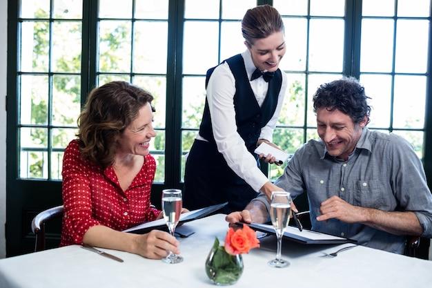 Официантка, помогающая паре при выборе меню