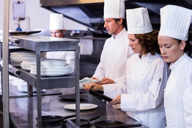 Команда поваров расставляет тарелки на станции заказа
