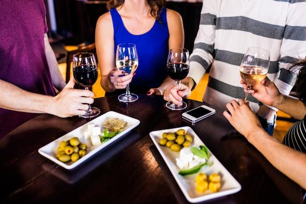 Друзья, имеющие аперитив с вином в баре