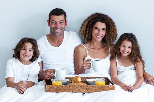 ベッドで朝食トレイに座っている家族の肖像