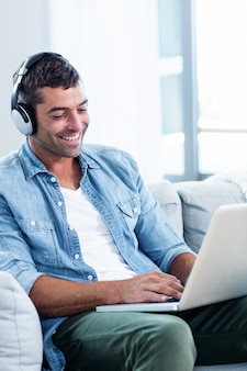 ラップトップを使用しながら音楽を聴く若い男