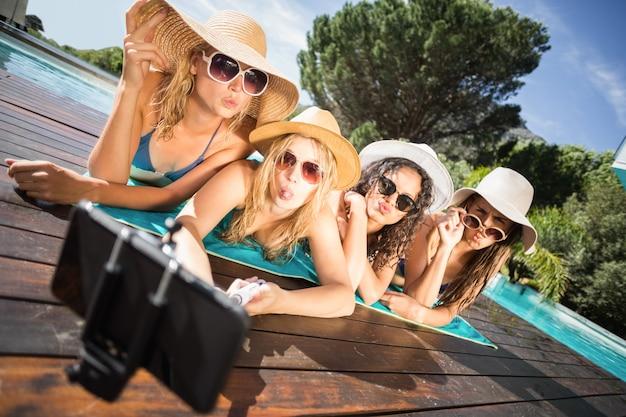 Счастливые друзья наслаждаются в бассейне