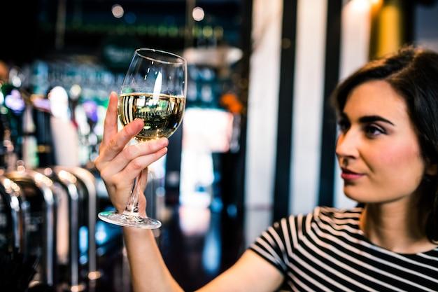 魅力的な女性は彼女のグラスワインをバーで見て