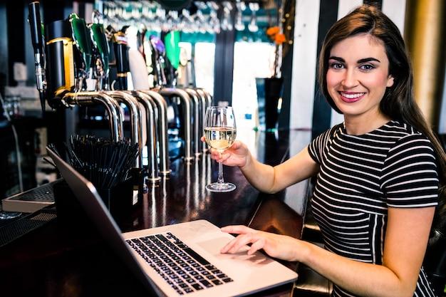 ラップトップを使用して、バーでワインのグラスを持っている魅力的な女性