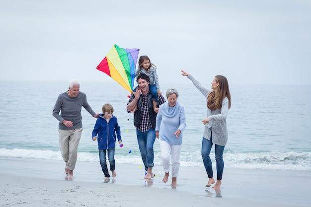 Семья нескольких поколений бежать на береге моря против неба