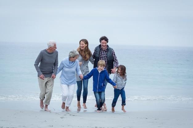 Счастливая семья из нескольких поколений наслаждается на берегу моря