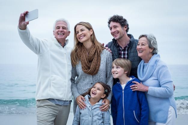 Дедушка принимает селфи с веселой семьей на берегу моря