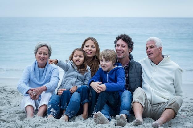 Семья смотрит в сторону, сидя на пляже