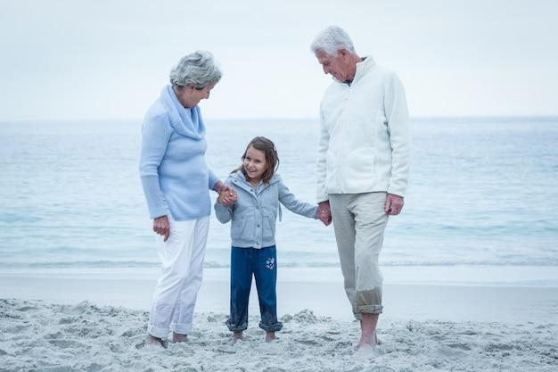 Бабушка и дедушка с внучкой на пляже