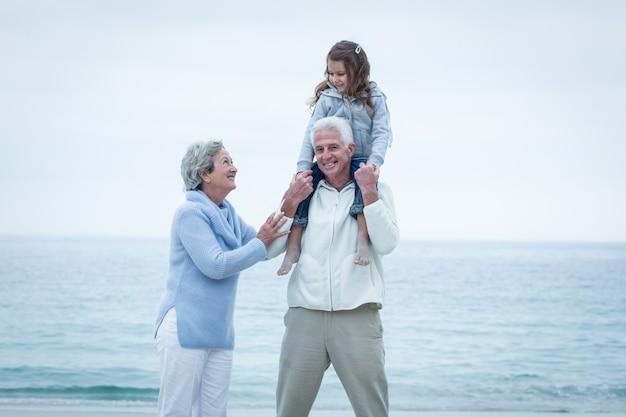 Бабушка и дедушка с внучкой наслаждаются на пляже
