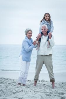 Улыбающиеся бабушка и дедушка с внучкой на пляже